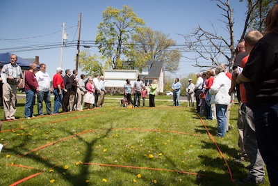 Volunteers and neighbors surrounded the future floor plan of the home to be build on a vacant lot on Penn Avenue.