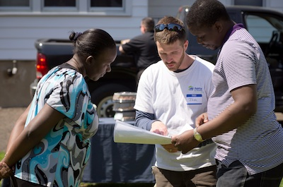 Habitat Construction Manager Josh Gieske reviews plans for the home with Loice and Zachariah Apela, one of the partner families.