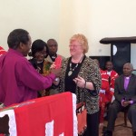 Bishop Stephen Munga presents a gift to Joanne Carlson.