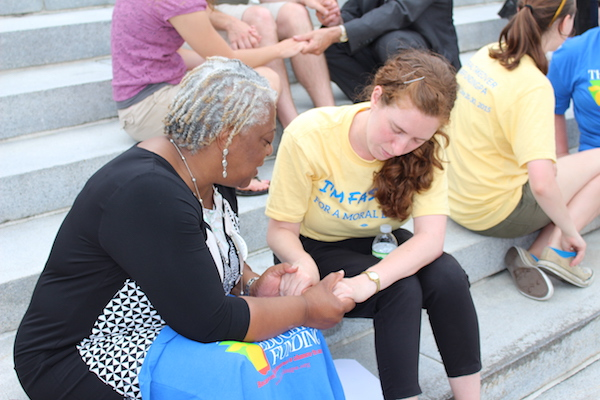 The Rev. Patricia Davenport, director for evangelical mission, prays with Cecily Harwitt, an organizer with POWER in the midst of a 10-day fast for a moral state budget.