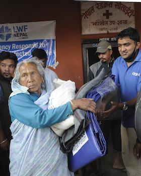 Volunteer distributes relief materials to earthquake victim at Jhaukhel in Bhaktapur. Photo: Dipesh Shrestha/LWF