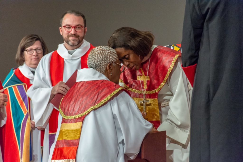 The Rev. Viviane Thomas-Breitfeld, elected the following day by the South Central Synod of Wisconsin as the ELCA's second African-American woman bishop, prays with Bishop Davenport during the installation.